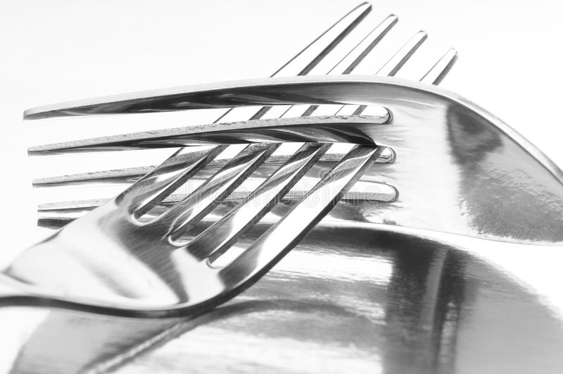 Two Intertwined Forks. Closeup of two forks with their tines intertwined on a reflective surface stock image