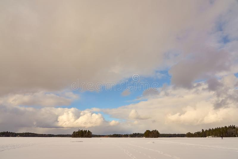 Two islands in the middle of Littoistenjärvi lake covered with ice and snow under a blue cloudy sky. royalty free stock images