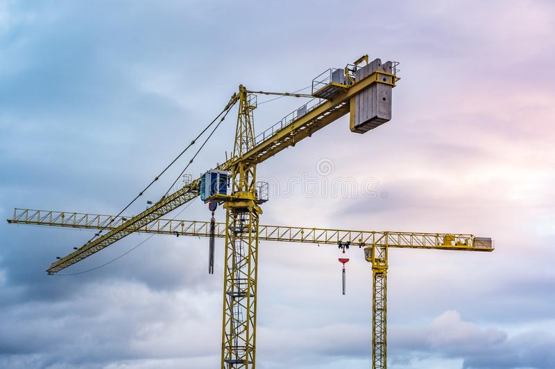 Two isolated cranes with the background of a wintry sky royalty free stock image