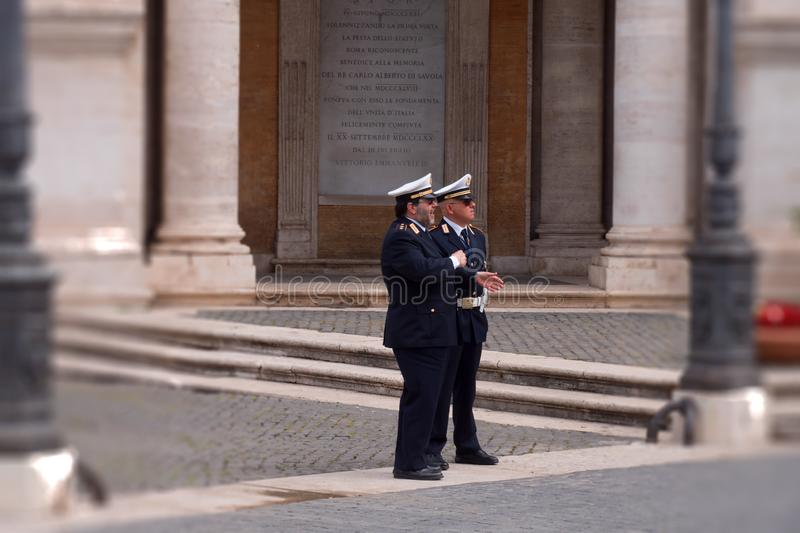 Siamese but vigilant - a visual joke. Two Italian carabinieri in the break, but ready to help if necessary, the tourists on the streets of Rome, ItalyCarabinieri stock images