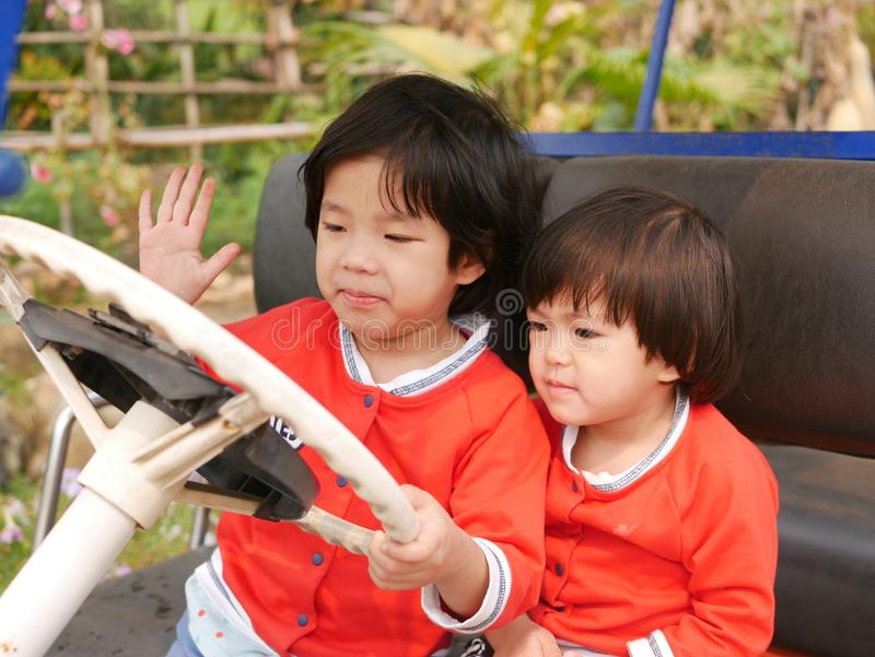 Two ittle Asian baby girls, sisters, holding on a steering wheel and pretending to drive a parking car. Pretend play enhances the baby`s development stock photography