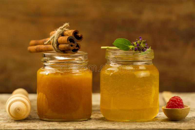Two jars of fresh honey with cinnamon, flowers, raspberries on wooden background. Two small jars of fresh honey with cinnamon, flowers, raspberries on wooden royalty free stock image