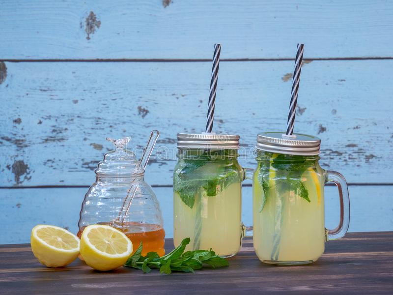 Two jars of fresh lemonade with sparkling water, mint and honey. Set on a dark oak table, with a blue barn wall in the background stock photos