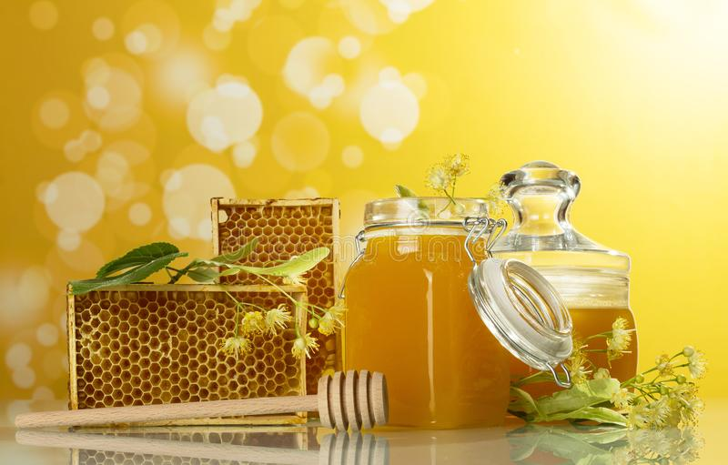 Two jars of honey, Linden flowers, wooden frames with honeycomb on yellow background royalty free stock image