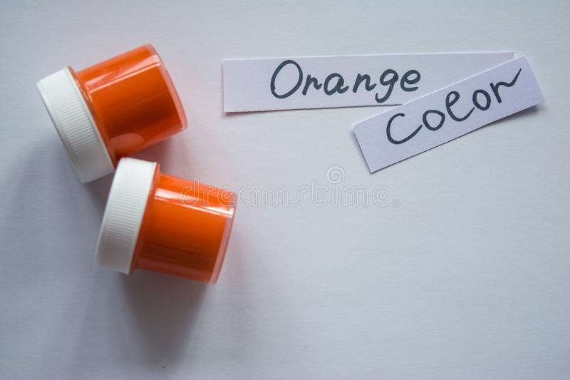 Two jars of orange paint with inscription on white paper - orange color with copy space stock photo