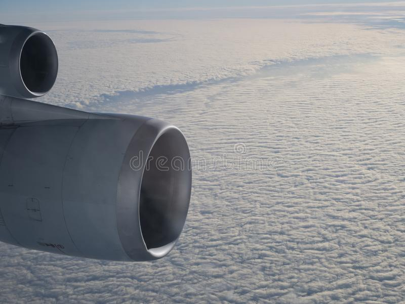 Two jet engines above cloud. Two jet engines at airline cruising height above layered cloud in sunshine stock images