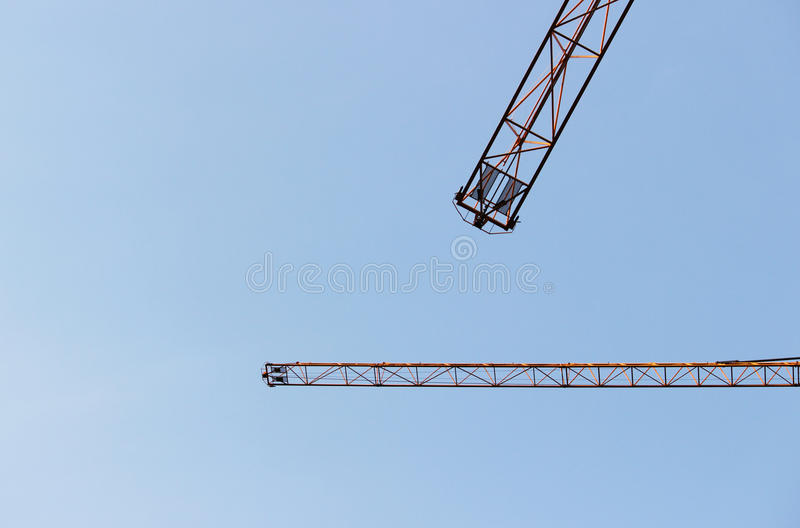 Two jib cranes against a cloudless blue sky. Two jib cranes against a cloudless blue sky royalty free illustration