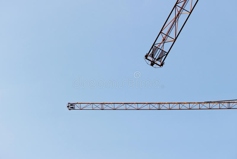 Two jib cranes against a cloudless blue sky. Two jib cranes against a cloudless blue sky vector illustration