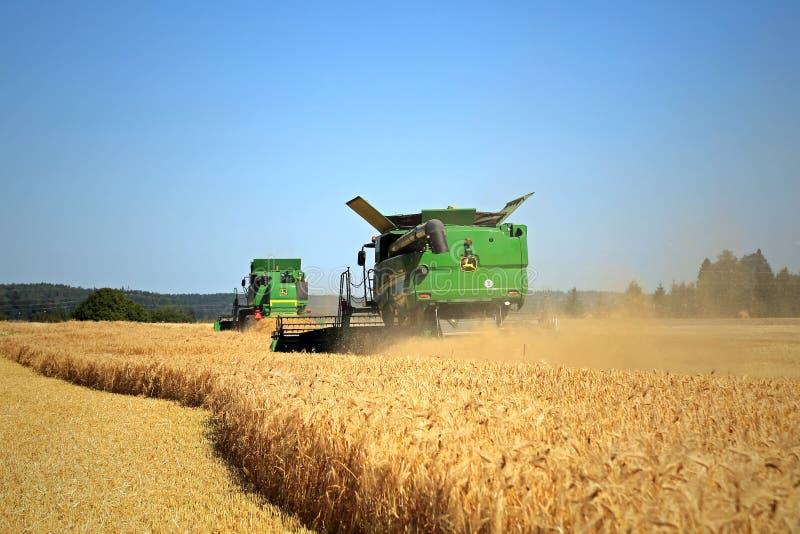 Two John Deere Modern Combines Harvest Barley stock image