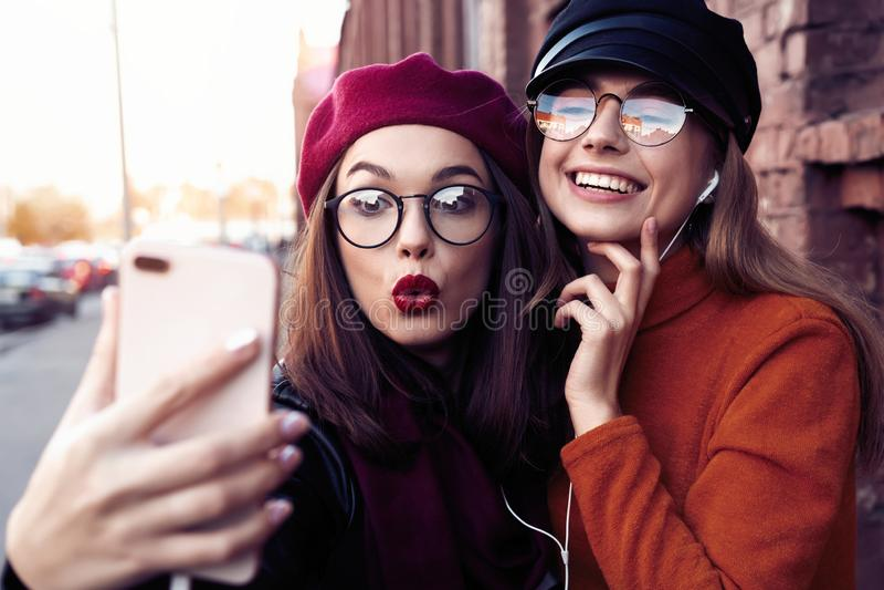 Two joyful cheerful girls taking a selfie while walking in the city street having fun. stock photos