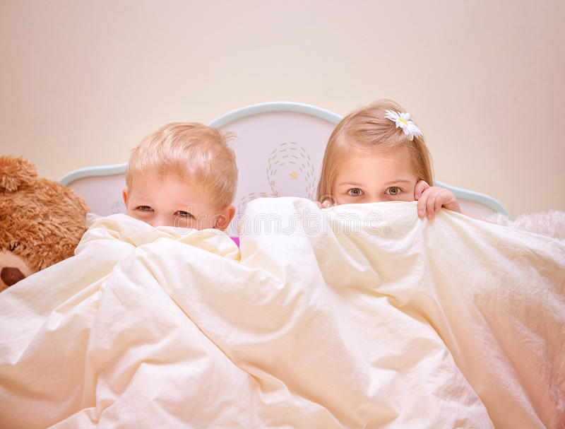 Two joyful kids playing game. In bedroom, siblings sitting on the bed and covered with blanket, hide and seek, happy childhood concept royalty free stock photo