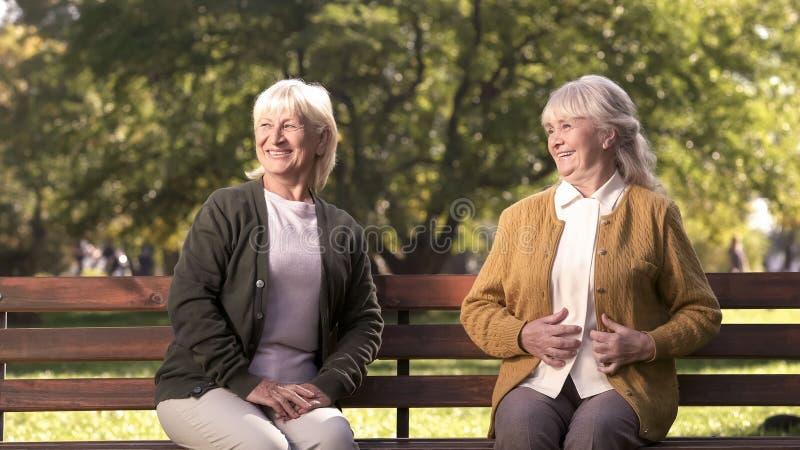 Two joyful senior women enjoying company of passerby people in park, elderly stock image