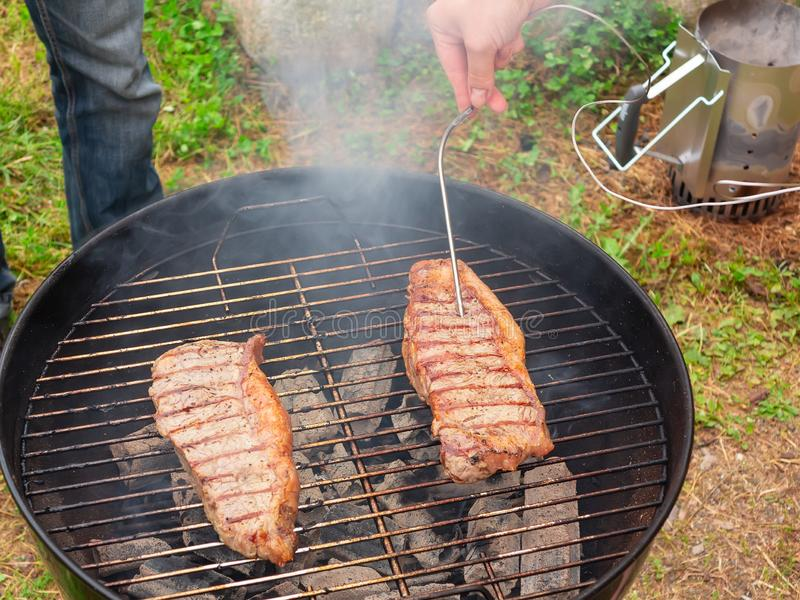 Two juicy beef steaks are grilled on a round grill. Meat readiness check royalty free stock photos
