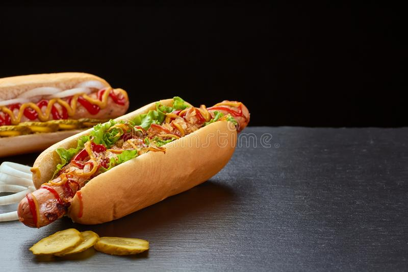 Two juicy hot dogs on dark slate background royalty free stock photo