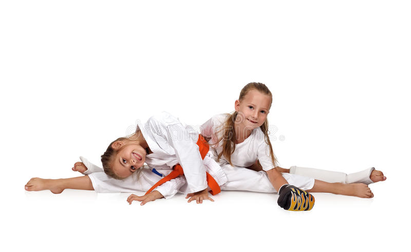 Two karate girl. Sitting on the splits stock photos