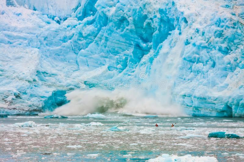 TWO KAYAKERS IN ICY WATER LOOKING AT ICEBERG CALVING NEARBY stock photo