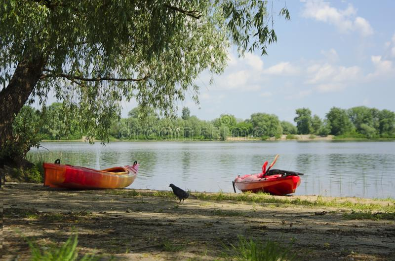 Two kayaks on a sandy beach near a beautiful river or lake in the evening. The concept of leisure, travel and water. stock photo