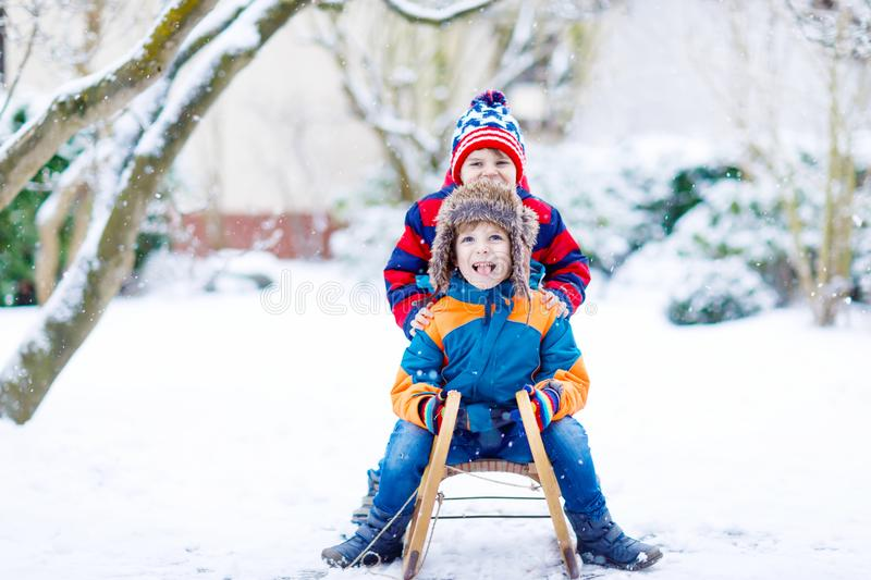 Two little kid boys enjoying sleigh ride in winter. Two kid boys enjoying sleigh ride during snowfall. Children sledding on snow. siblings riding a sledge. twins royalty free stock images