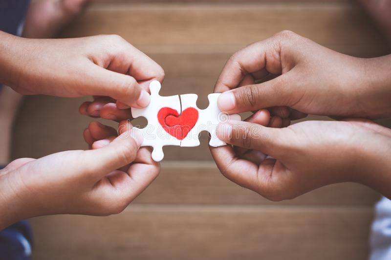 Two kid hands connecting couple jigsaw puzzle with drawn red heart. Two kid hands connecting couple jigsaw puzzle piece with drawn red heart royalty free stock image
