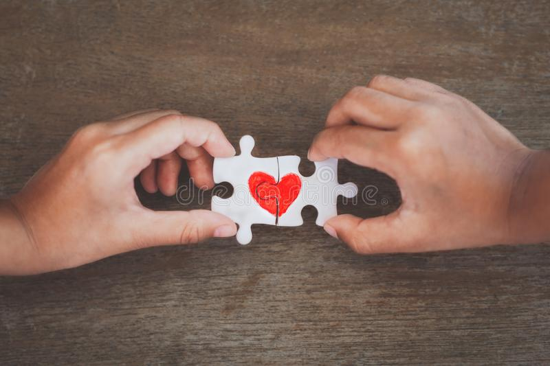 Two kid hands connecting couple jigsaw puzzle with drawn red heart. Two kid hands connecting couple jigsaw puzzle piece with drawn red heart royalty free stock photos