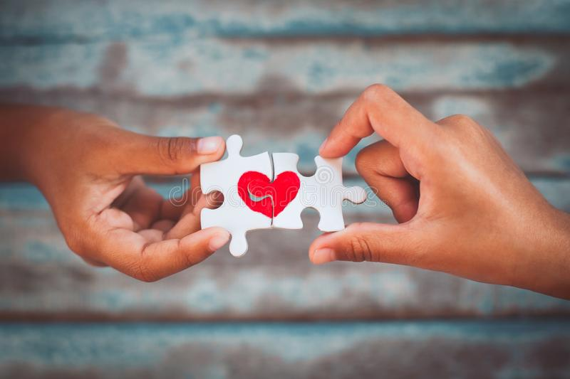 Two kid hands connecting couple jigsaw puzzle with drawn red heart. Two kid hands connecting couple jigsaw puzzle piece with drawn red heart royalty free stock images