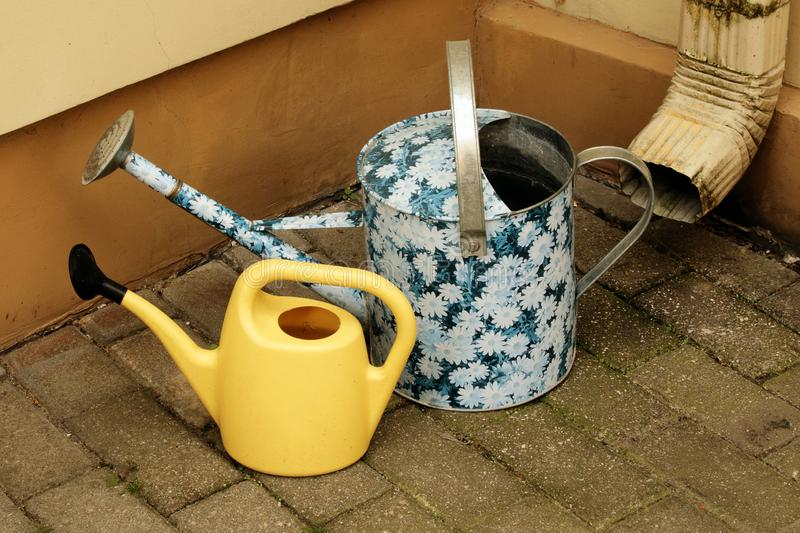 Two kid& x27;s watering cans outside near water drainage pipe on tiled yard pavement. Two kid& x27;s watering cans outside near water drainage pipe, spring royalty free stock images