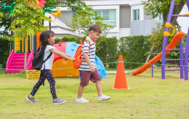 Two kid school children walking at playground in kindergarten pr. Eschool.back to school royalty free stock photo