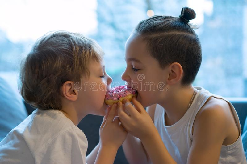 Two kids bite off a donut and having fun. two boys together bite from the donut. children enjoy a donut with strawberry stock images