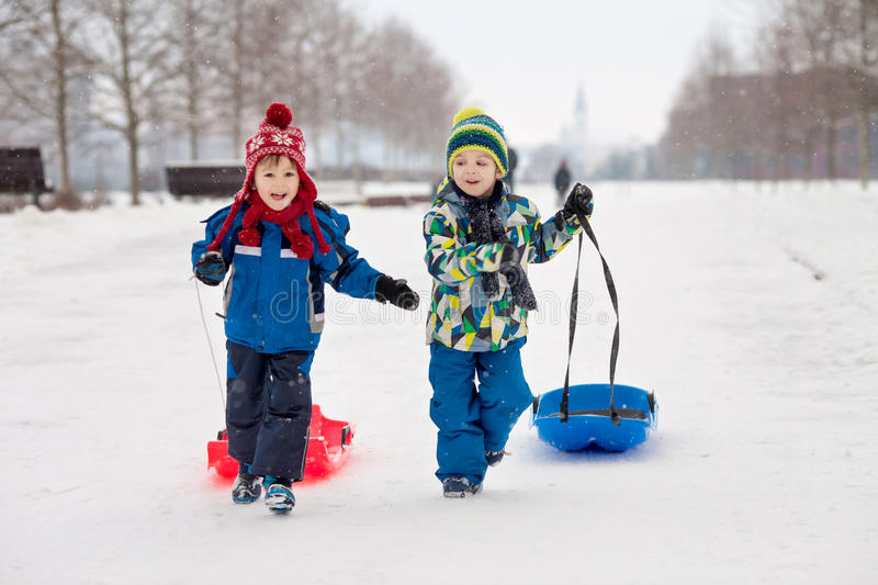 Two kids, boy brothers, sliding with bob in the snow, wintertime. Happiness concept stock photos