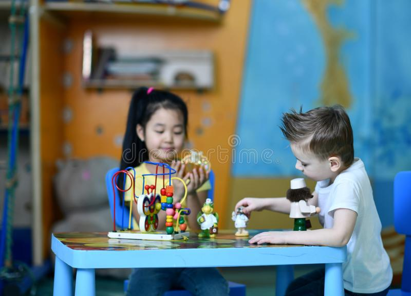 Two kids boy and girl play enthusiastically at the table toy doctors stock images