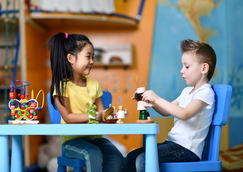 Two kids boy and girl sit at the table and play toy doctors stock photos
