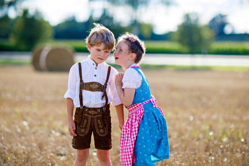 Two kids, boy and girl in traditional Bavarian costumes in wheat field stock image