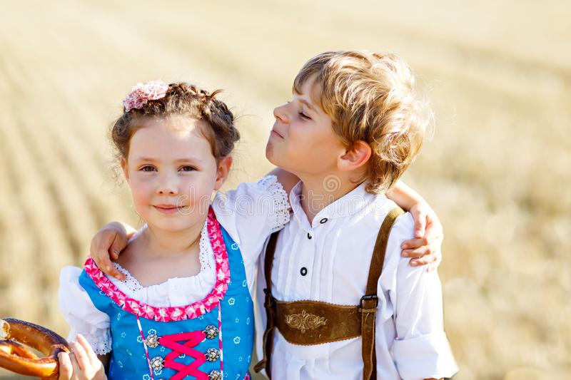 Two kids, boy and girl in traditional Bavarian costumes in wheat field stock photography