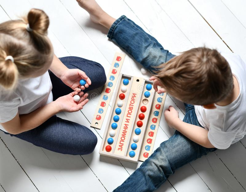 Two kids boy and girl in white t-shirts and blue jeans play educational game remember and repeat. With red blue and white balls sitting on white wooden floor royalty free stock photo