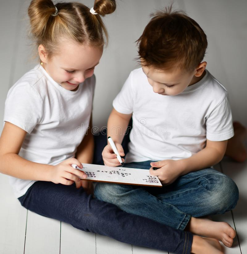 Two kids boy and girl in white t-shirts and blue jeans sit close to each other and play word game with black markers on plate stock photography