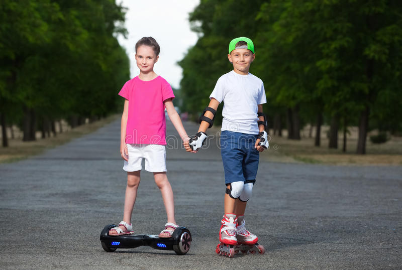 Two kids boy on roller skates and girl on self-balancing scooter wrapped stock images