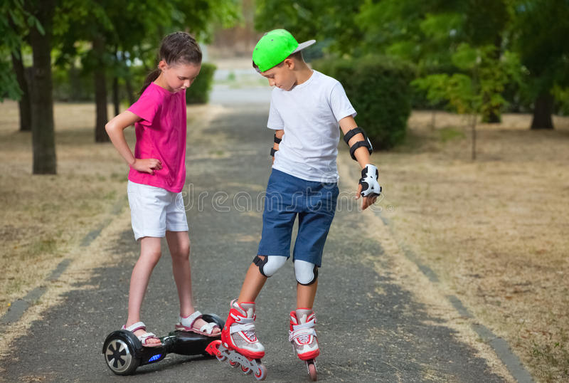 Two kids boy on roller skates and girl on self-balancing scooter wrapped stock photos