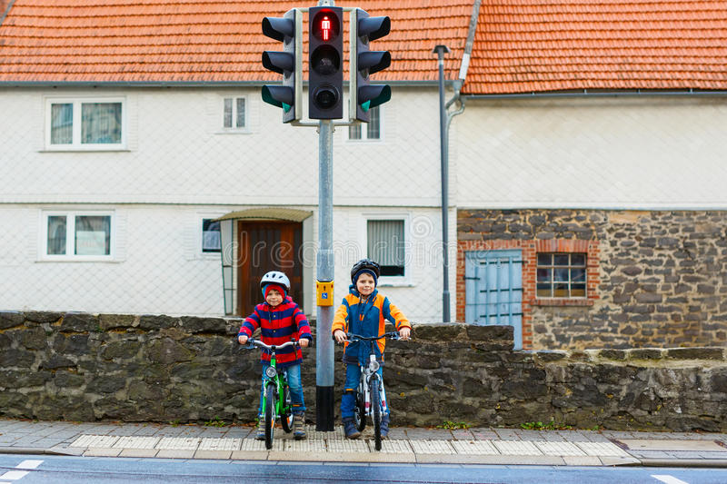 Two kids boys biking and waiting on traffic light. Two active kids boys in helmet biking on bicycles in the city. Happy children in colorful clothes and waiting royalty free stock photo