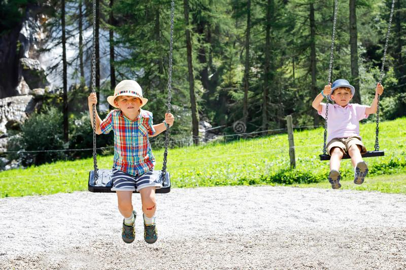 Funny kid boy having fun with chain swing on outdoor playground while being wet splashed with water. Two kids boys having fun with chain swing on outdoor royalty free stock images