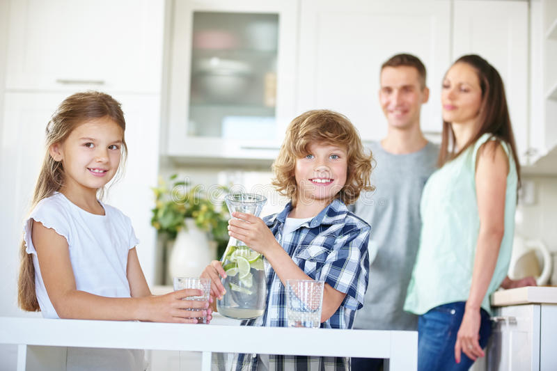 Two kids with carafe full of fresh water. Two kids with carafe drinking fresh water with lime in the kitchen stock photos