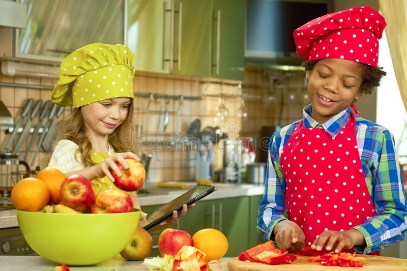 Two kids cooking. Little girl with tablet. Online recipe book stock photography