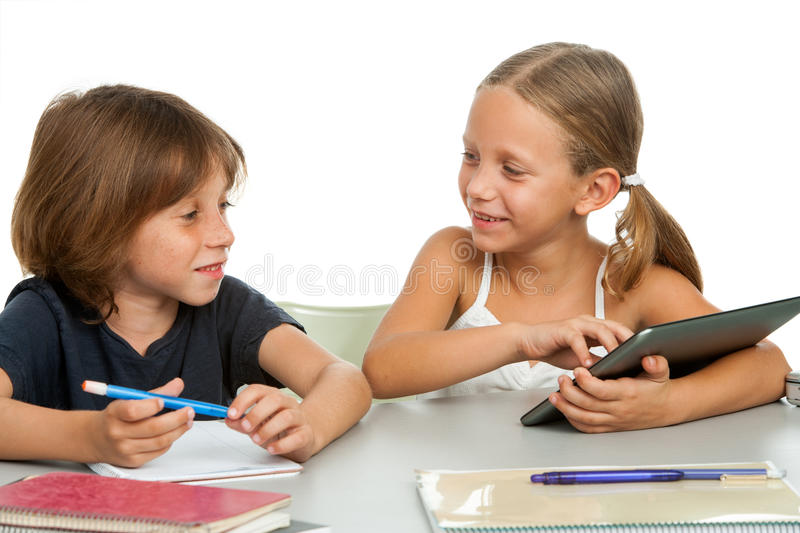 Two kids discussing homework at desk.