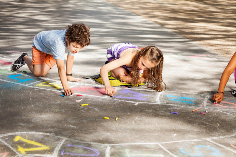 Two kids draw outside in chalk hopscotch. Group of kids draw with chalk on the asphalt floor stock photography