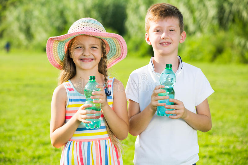 Two kids drinking water. Happy two kids in elementary school age drinking water from plastic bottle in green park royalty free stock photos