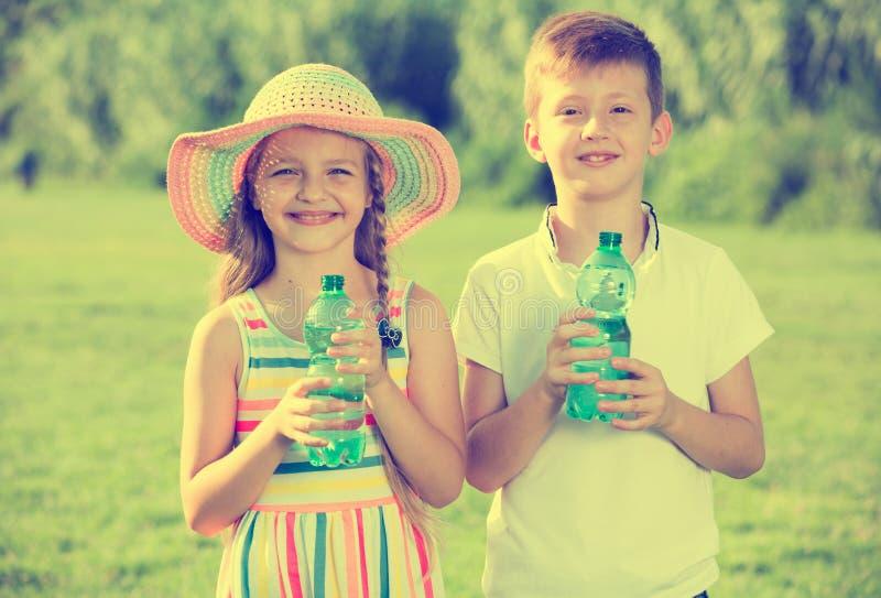 Two kids drinking water. Happy two kids in elementary school age drinking water from plastic bottle in green park stock photo