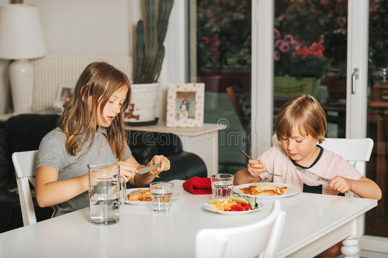 Two kids eating lasagna for lunch. Healthy home made meal for children stock image