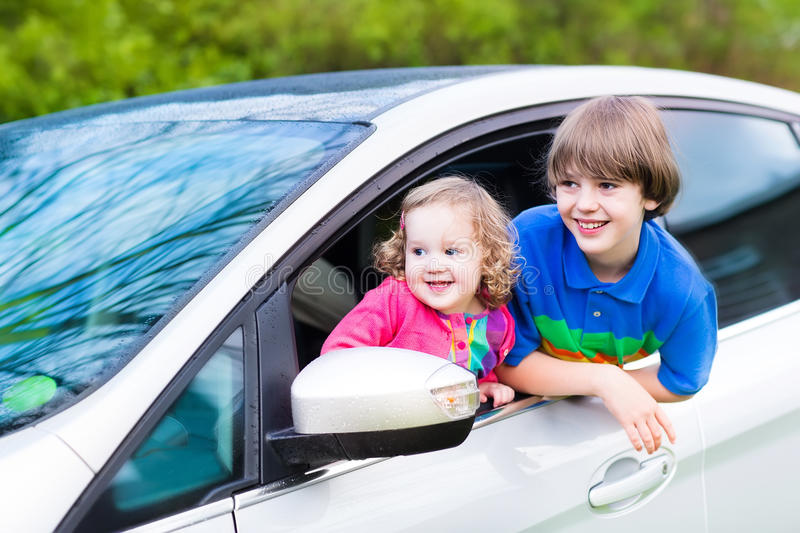 Two kids enjoy vacation car ride on summer weekend. Two kids, school age boy and cute curly toddler girl, enjoy vacation car ride on a summer weekend watching stock photo