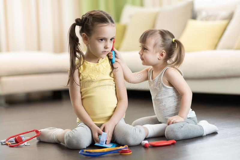 Two kids, smiling toddler girl and her older sister, playing doctor and hospital using medical toys, having fun at home. Two kids, funny toddler girl and her royalty free stock image