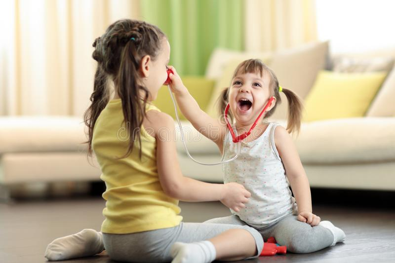 Two kids sisters playing doctor at home. Child girl examining older sister. stock image