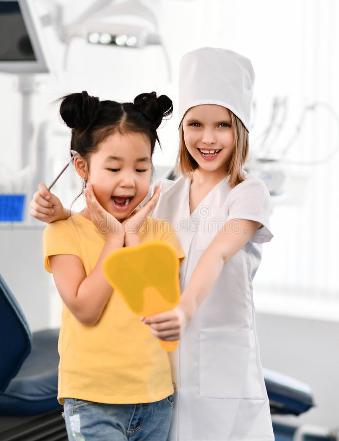 Two kids girls play dentist and happy patient in dental office. royalty free stock images